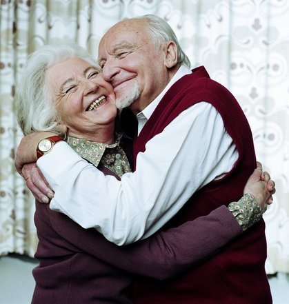 Mature couple embracing, smiling, close-up