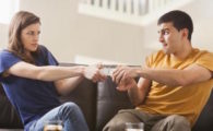 Couple arguing over remote on sofa